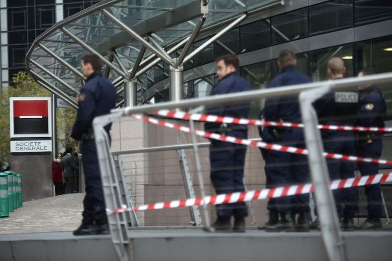<p>Police stand outside the entrance of the headquarters of the Société Générale bank in the La Défense business district, on the western outskirts of Paris on November 18, 2013, where a number of gun shots were fired and no one was injured. The incident comes several hours after a 27-year-old man was left fighting for his life after being shot by an intruder at the Paris offices of left-wing French daily Libération.</p>