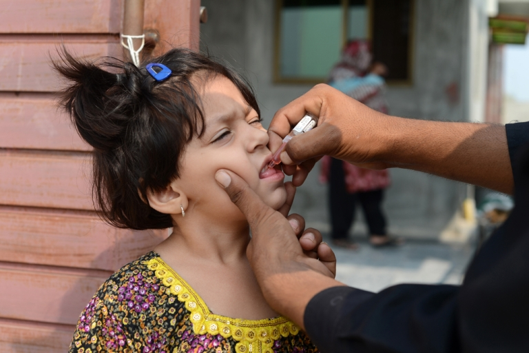 <p>A Pakistani child receives an oral polio vaccine during an anti-polio campaign in Rawalpindi on October 1, 2013.</p>