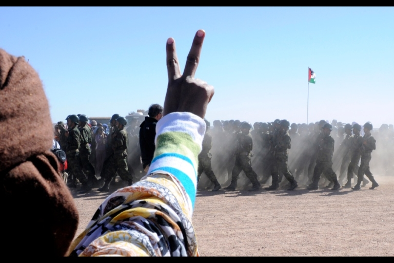 <p>A man flashes a victory sign as soldiers from the pro-independence Polisario Front parade on Feb. 27, 2011 to celebrate the 35th anniversary of the proclamation of independence of the Democratic Arabic Sahrawi Republic, in the Western Sahara village of Tifariti.</p>