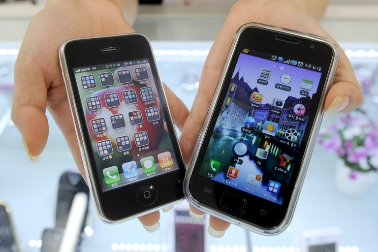 <p>A South Korea shop manager shows Samsung Electronics' Galaxy S mobile phone (R) and Apple's iPhone 3G in July, 2010. Although Samsung has been ordered to pay nearly a billion dollars to Apple for patent infringements, the two companies remain dependent on one another.</p>