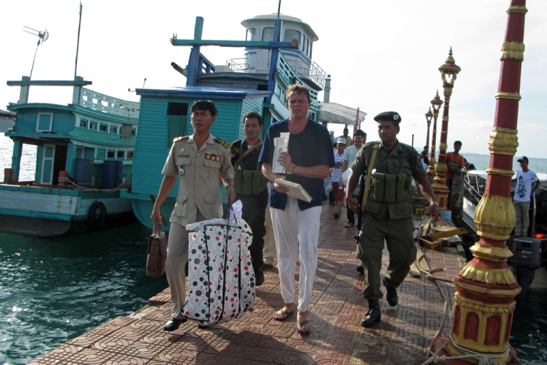 <p>Russian tycoon Sergei Polonsky (C) walks along with police officers after his arrest in Sihanoukville, southern Cambodia, on November 11, 2013.</p>
