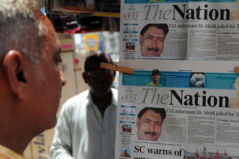 <p>A man reads newspapers bearing photographs of Pakistani Dr. Shakil Afridi, recruited by the CIA to help find Osama bin Laden, at a newsstand in Karachi on May 25, 2012.</p>