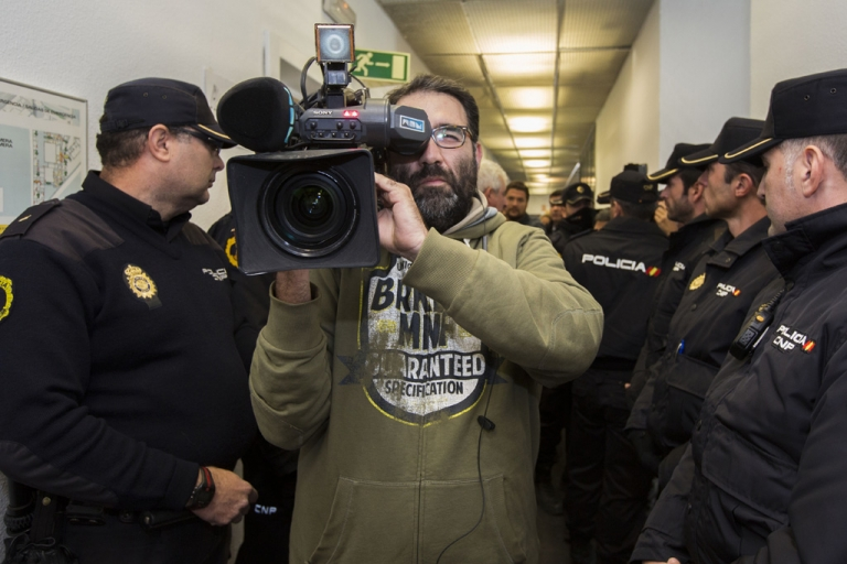 <p>A man films as police officers expel workers of Spanish television station Channel 9, part of Valencia broadcaster RTVV, from the company's headquarters on November 29, 2013, following the closure of RTVV. The debt-laden Spanish television station went abruptly off the air, apparently cut off by authorities as laid-off staff protested live in defiance of orders to shut it down.</p>
