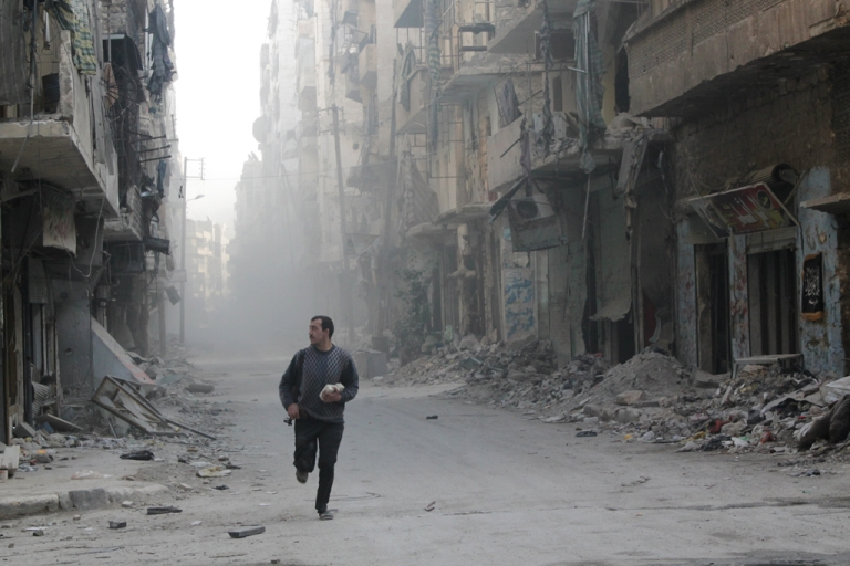 <p>A rebel fighter from the Free Syrian Army runs in a street of Aleppo's Salah al-Din neighbourhood during fighting against Syrian government forces on November 18, 2013.</p>