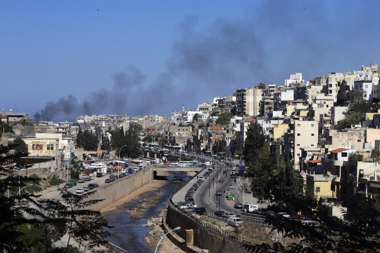 <p>Smoke billows from Tripoli's Bab al-Tabbaneh Sunni neighborhood on Oct. 25, 2013 during clashes with Alawite supporters of Syrian President Bashar al-Assad. Sunni militants in Lebanon accuse the army of siding with supporters of the Syrian regime.</p>