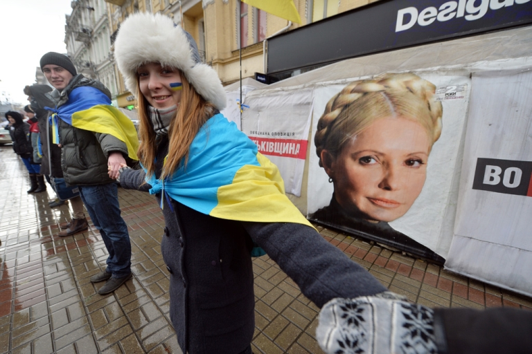 <p>Ukrainian students stand hand-in-hand to create a human chain symbolizing the unity of Ukraine with the EU in front of the tents set up by supporters of Yulia Tymoshenko in Kiev on November 2013.</p>