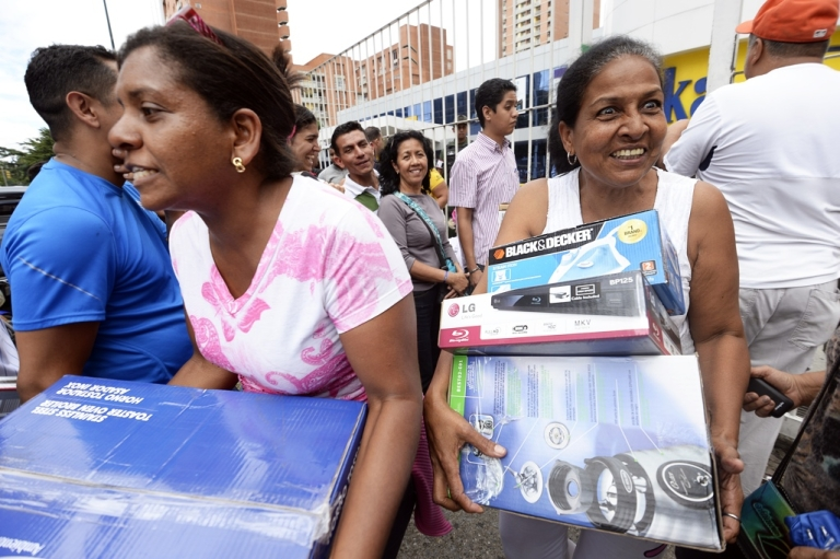 <p>Shoppers loaded with purchases leave a Daka store in Caracas on Nov. 9. Venezuelan President Nicolas Maduro ordered the state occupation appliances stores accused of hiking prices.</p>