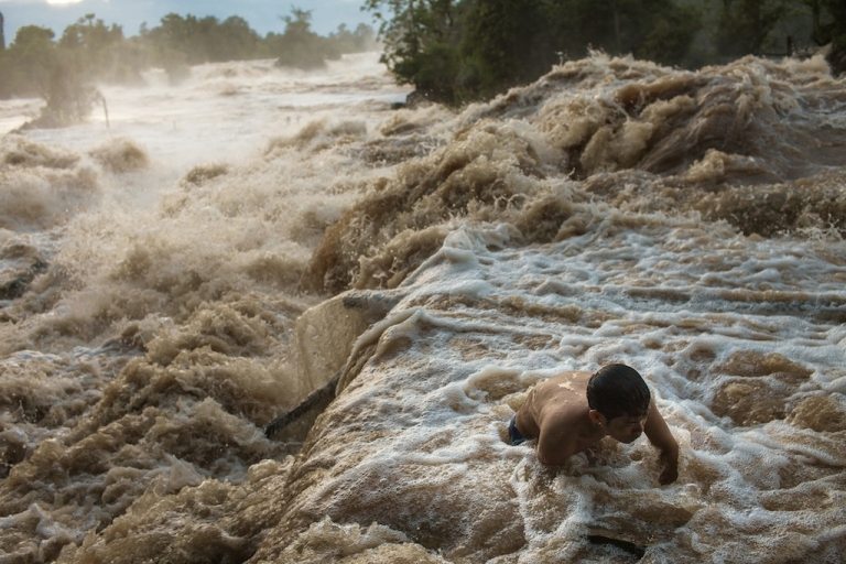 <p>A fisherman fights the current of Khone Phapheng falls to clean debris from a
