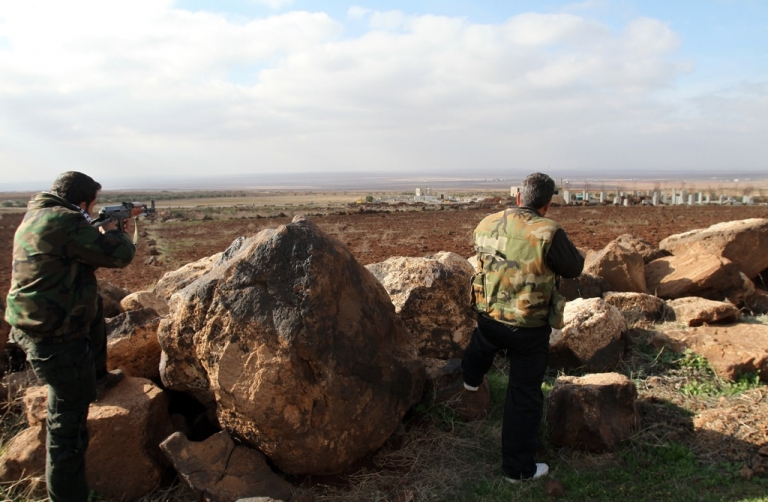 <p>Syrian soldiers point their rifles towards the rebel-held province of Daraa from their position in the southern city of Sweida on January 23, 2013.</p>