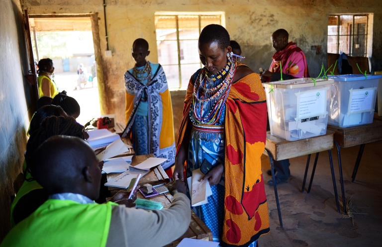 <p>A Maasai woman collects her papers before voting in Ilngarooj, Kajiado County, Maasailand, on March 4, 2013 during the first nationwide elections since the violence-wracked polls five years ago.</p>