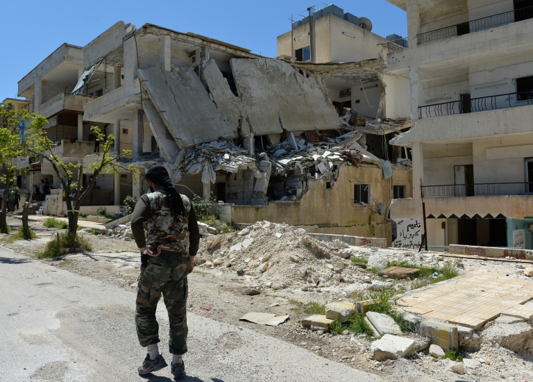 <p>A Syrian rebel walks past a destroyed building in Salma in the coastal province of Latakia on April 26, 2013.</p>