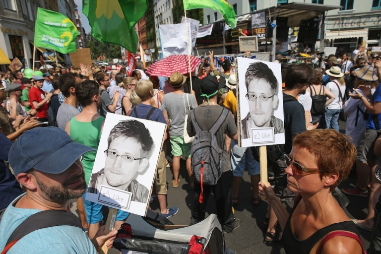 <p>Participants demonstrate in support of former NSA employee Edward Snowden at a protest march against the electronic surveillance tactics of the NSA on July 27, 2013 in Berlin.</p>