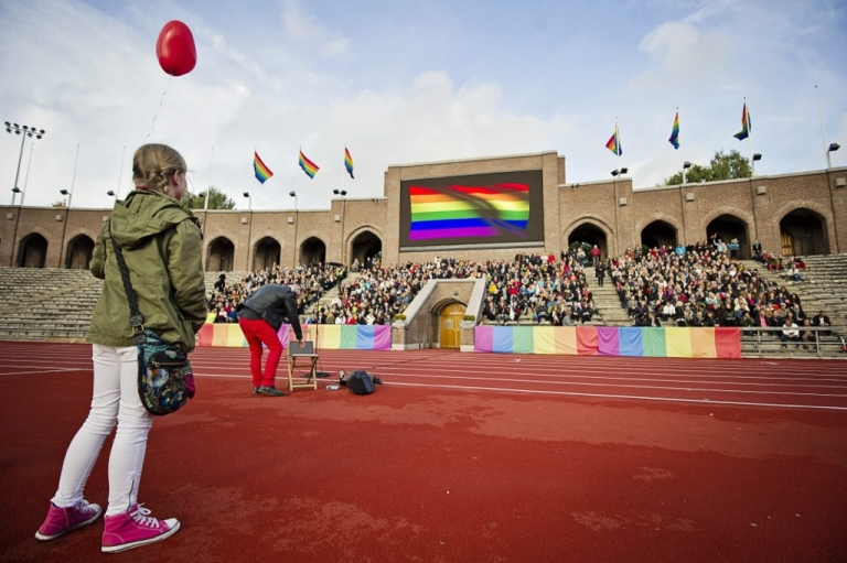 <p>People sing the Russian National Anthem at the Stockholm Olympic Stadium on October 6, 2013 while raising rainbow flags in solidarity with the Russian LGBT community. A project called 'Live and Let Love' will use footage from the event to be cut together with other singers and musicians from around the world to make a video film that will be shown on YouTube ahead of the winter Olympic games in Sochi.</p>