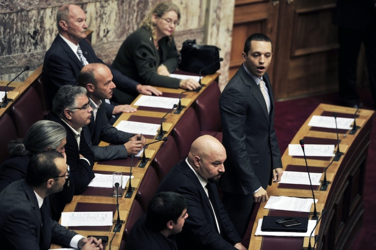 <p>Golden Dawn party spokesman Ilias Kassidiaris speaks next to the party's lawmaker Ilias Panagiotaros at the Greek parliament on October 16, 2013, prior to the vote to lift the immunity from prosecution of six lawmakers from the Golden Dawn party.</p>