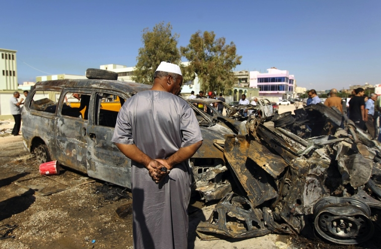 <p>Benghazi residents gather at the site of a car blast in the parking lot of school used as an electoral office on October 26, 2013.</p>