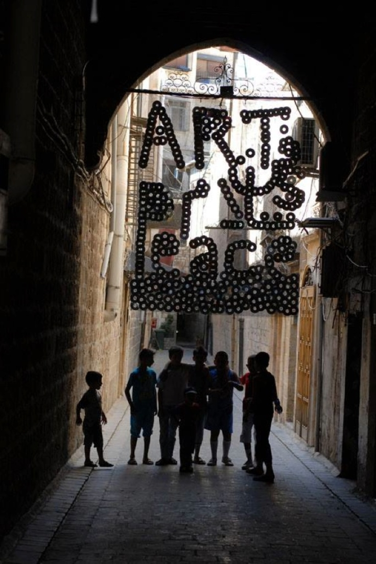 <p>Children stand on July 20, 2013 in the Old City of Aleppo, under an installation that was part of Issa Touma's Art Camping initiative.</p>