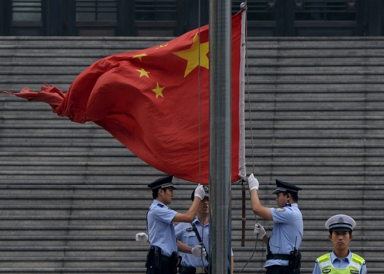 <p>Police raise the Chinese flag outside the Intermediate People's Court in Jinan, Shandong province, on Sept. 22, 2013.</p>