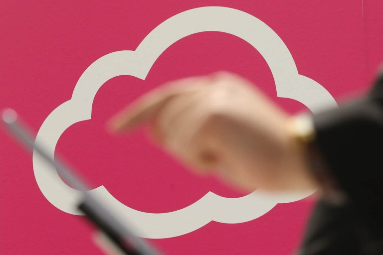 <p>A visitor tries out a tablet computer next to a cloud computing and technology symbol at the Deutsche Telekom stand at the 2013 CeBIT technology trade fair on March 5, 2013 in Hanover, Germany.</p>