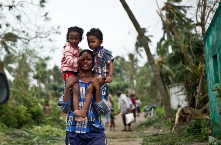 <p>A displaced Indian man carries his children at Sonupur village around 15 kms from Gopalpur on October 13, 2013. Cyclone Phailin left a trail of destruction along India's east coast and up to seven people dead after the biggest evacuation in the country's history helped minimise casualties.</p>