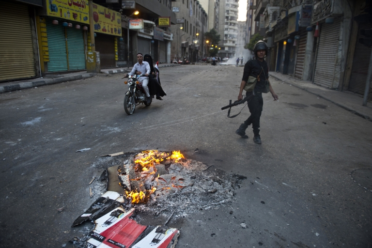 <p>An Egyptian riot policeman takes position in Al-Jumhuria street in downtown Cairo during clashes with Muslim Brotherhood supporters of Egypt's ousted Islamist president Mohamed Morsi on October 6, 2013.</p>
