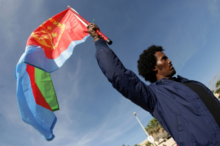 <p>A man waves an Eritrean flag  on October 21, 2013 in the southern Sicilian city of Agrigento during a ceremony commemorating the migrants who drowned off the southern Italian islad of Lampedusa.</p>