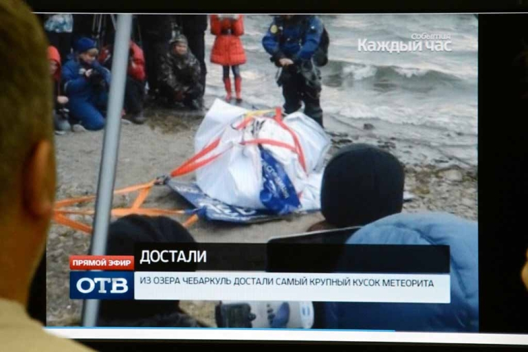 <p>Men watch a computer screen in Moscow on Oct. 16, 2013, as a team of divers pull a 1.5-metre-long (five-foot-long) suspected meteorite from Lake Chebarkul in the Chelyabinsk region. It is said to have been part of a meteor whose ground-shaking shockwave hurt 1,200 people in February.</p>
