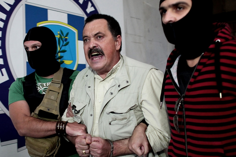 <p>Christos Pappas (2nd-R), lawmaker of the extreme far-right Golden Dawn party, is escorted by masked police officers to the prosecutor's office from the police headquarters in Athens.</p>