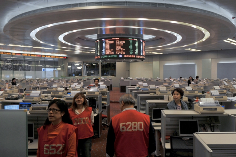 <p>Traders walk the floor of the Hong Kong Stock Exchange on March 2012.</p>