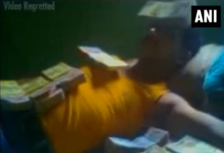 <p>Indian Communist Party politician Samar Acharjee is seen lying in a bed of $24,000 in cash. A friend took a cellphone video of Acharjee covered in rupee notes that has now gone viral and cost the 43-year-old his position with the political party.</p>
