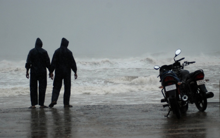<p>Indians watch the high tide at Gopalpur beach on Oct. 12, 2013.</p>