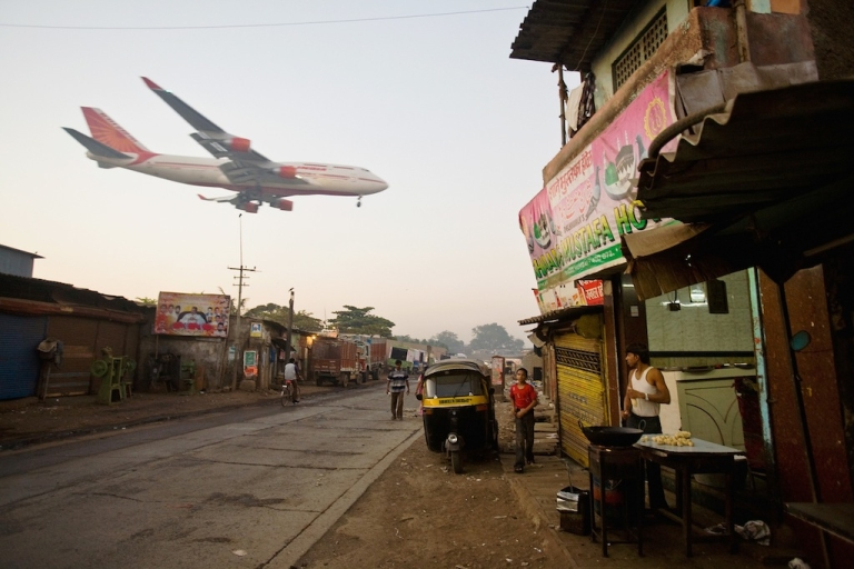 <p>A man makes chapatis as an Air India jet approaches Mumbai Airport. Economists debate whether a cheaper rupee will mean more tourists at India's famed Taj Mahal.</p>