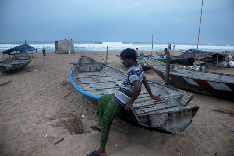 <p>An Indian fisherman sits on his boat on a beach near Gopalpur in the eastern state of Orissa on Oct. 11, 2013. Authorities have asked fishermen to stay ashore as Cyclone Phailin barrels toward the coast.</p>
