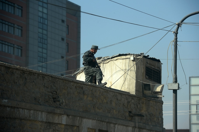 <p>An Afghan policeman stands guard over the compound of the police headquarters in Kabul on Dec. 24, 2012.</p>