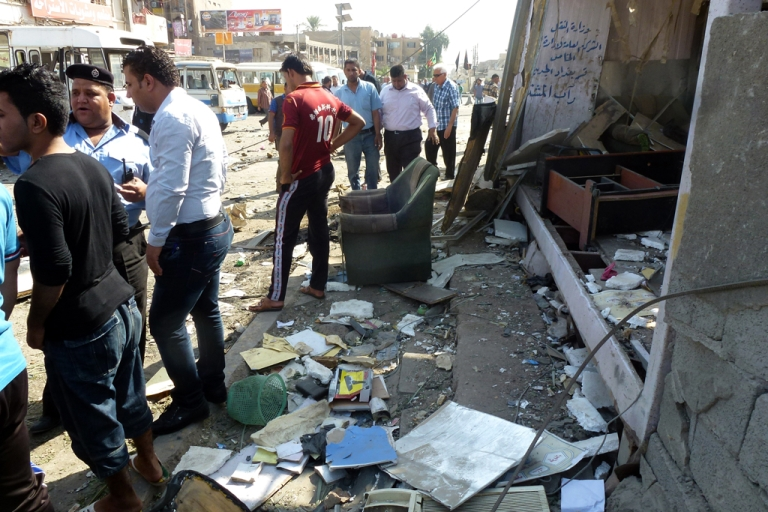 <p>Iraqis gather at the scene of an explosion at a small bus station on October 27, 2013, in the the Mashtal district of the capital Baghdad.</p>
