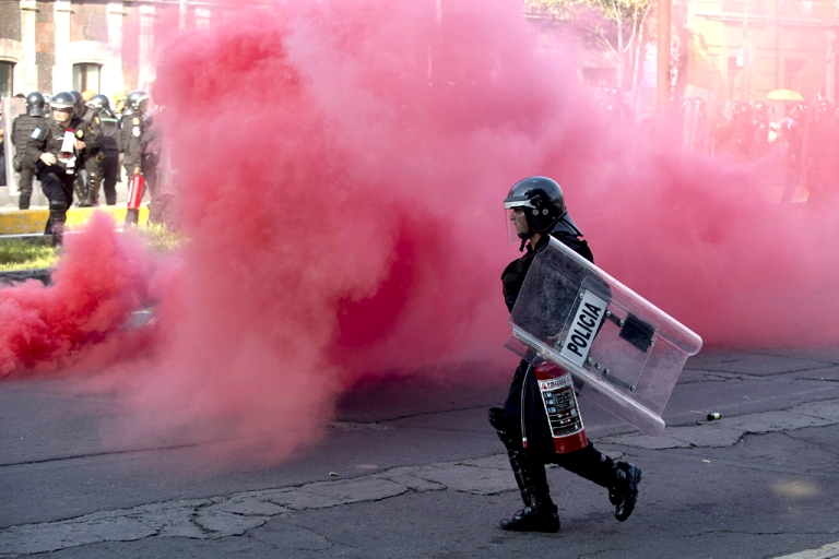<p>Riot police throw smoke grenades during clashes with students along Reforma Avenue in Mexico City on October 2, 2013.  Mexican students marched to commemorate the anniversary of the Tlatelolco massacre of university students.</p>