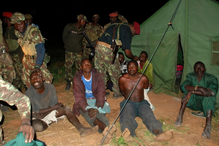 <p>A picture taken on October 17, 2013 shows prisoners belonging to former Mozambican rebel movement Renamo sitting on the ground with government soldiers guarding them in Gorongosa.</p>
