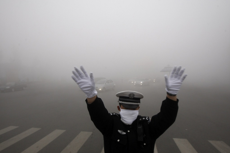 <p>A policeman directs traffic in thick smog in China's northeastern city of Harbin on Oct. 21, 2013.</p>