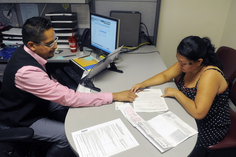 <p>Enrollment Specialist Horacio Castaneda, left, helps Rosa Ayala Cruz, right, apply for health benefits at the Denver Health Westside Family Health Center on Oct. 1, 2013 in Denver, Colo.</p>