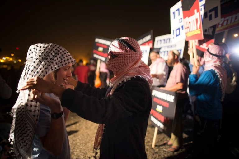 <p>Israeli youths wear keffiyehs, traditional Palestinian scarfs, as right wing Israelis demonstrate against the release of 26 Palestinian prisoners on Oct. 29, 2013 outside Ofer military prison on the outskirts of Jerusalem. The prisoners are to be freed as part of the terms of renewed US-brokered peace talks.</p>