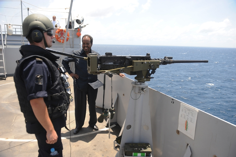 <p>Somali President Hassan Sheikh Mohamud (C) stands onboard a Dutch Amphibious Assault warfare ship part of the EU Naval Force off the coast of Mogadishu on September 5, 2013. The ship, part of the EU naval taskforce whose role is to thwart any potential pirate attacks in the region.</p>