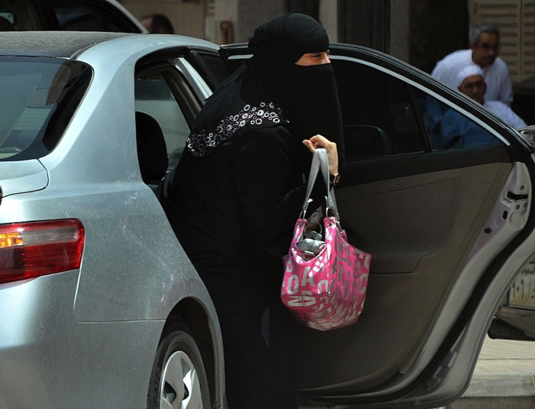 <p>A Saudi woman gets out of a car after being given a ride by her driver in Riyadh on May 26, 2011.</p>