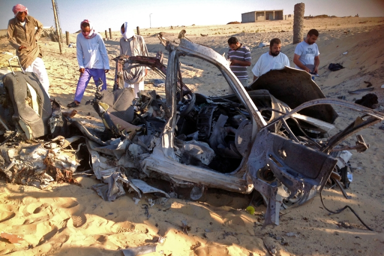 <p>Egyptians gather near a damaged car bomb that detonated before reaching the intended target killing three passengers on July 24, 2013,in El-Arish in Egypt's Sinai peninsula. The bomb went off as the assailants entered the north Sinai town of El-Arish, where two soldiers were killed in separate shooting attacks earlier, said security officials.</p>