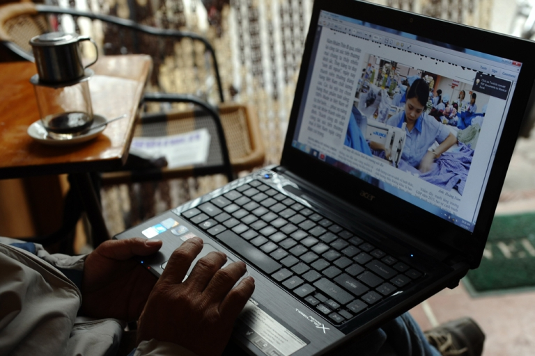 <p>A man reading online news with his laptop at a coffee shop in downtown Hanoi, Vietnam.</p>