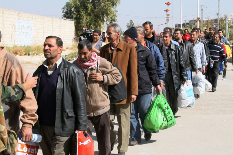 <p>Syrian civilians evacuate the war-battered suburb of Damascus, Moadamiyet al-Sham, with the help of the Social Affairs Ministry, as fighting between pro-government troops and rebel fighters continues in districts of the capital.  AFP PHOTO/STR        (Photo credit should read -/AFP/Getty Images)</p>