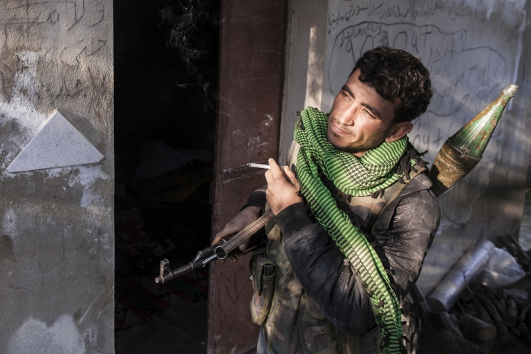 <p>A defected Syrian soldier, now a member of the Free Syrian Army, stands outside a mountain outpost near the village of Janudieh in the northern province of Idlib on March 20, 2012.</p>