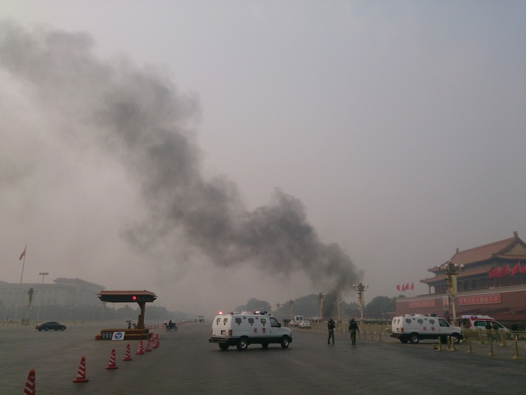 <p>Police cars block off the roads leading into Tiananmen Square as smoke rises from a deadly car crash on Oct. 28, 2013.</p>