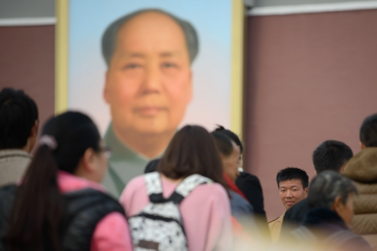 <p>A plainclothes policeman (centre R) observes as tourists enter the Forbidden City beneath a portrait of Mao Zedong (top) at Tiananamen gate in Beijing on October 31, 2013. A Uighur group dismissed Beijing's account of a
