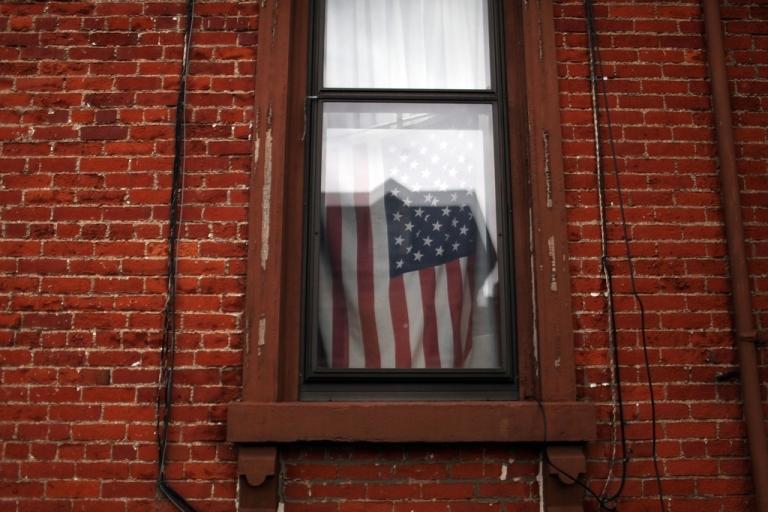 <p>A flag hangs in a window in Utica, NY.</p>