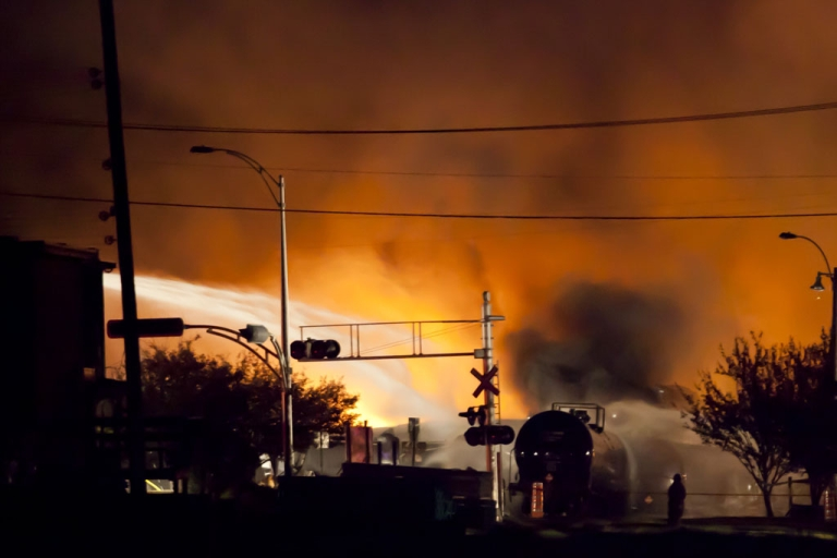 <p>Firefighters douse flames after a freight train loaded with oil derailed in the Canadian town of Lac-Megantic, Que., on July 6, 2013. Investigators announced on Sept. 11, 2013, that oil inside the tankers was mislabelled and was more dangerous and combustible than believed.</p>