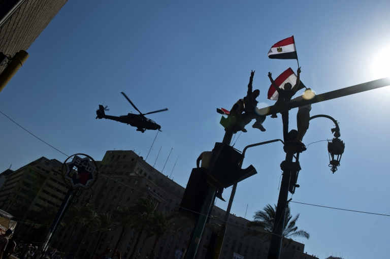 <p>Supporters of army chief General Abdel Fattah al-Sisi wave the Egyptian flag as an army helicopter flies over Tahrir Square in Cairo on July 16, 2013. Egypt's authorities formally detained Mohamed Morsi on suspicion of collaborating with Palestinian militants in murdering policemen and staging prison breaks, as tens of thousands of the deposed president's supporters and opponents staged rival rallies.</p>